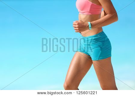 Runner running with heart rate monitor sports smart watch. Smartwatch bracelet and athlete body midsection closeup. Fitness girl training fit legs on summer beach. Healthy active living.