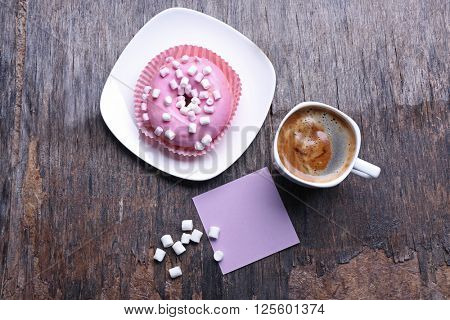 Cup of coffee, doughnut, marshmallows and blank piece of paper on wooden background