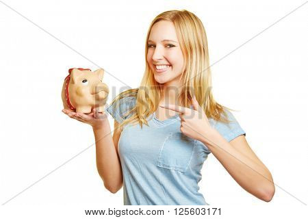 Young smiling woman pointing to money in her piggy bank