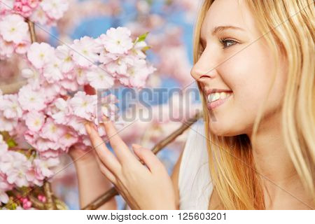 Happy blonde woman enjoying scent of blooming cherry blossoms