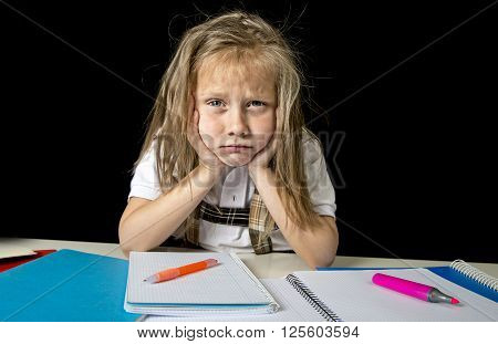 sad and tired cute junior schoolgirl with blond hair sitting in stress working doing homework looking bored and overwhelmed in children education at school and low academic performance