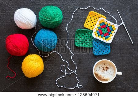 Balls of white, red, green, yellow and blue yarn, crocheted motifs and a cup of coffee on grunge black background.