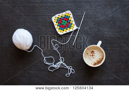 White yarn, crocheted multi-colored motif and coffee on grunge black background.