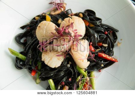 Black squid ink pasta is paired with scallops on pasta dish