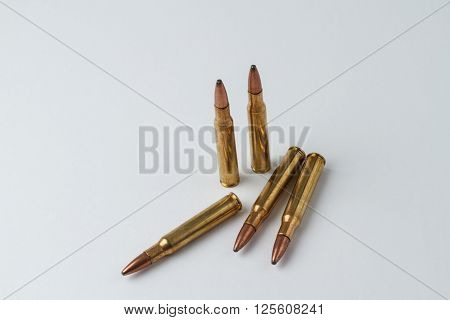 Five .30-06 caliber hunting rifle ammunition cartridges in a random arrangement