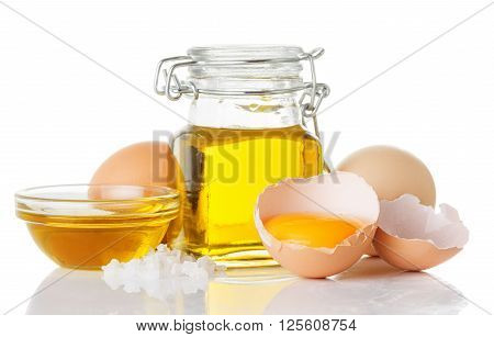 Ingredients for homemade mayonnaise olive oil in a bottle raw eggs salt isolated on white background