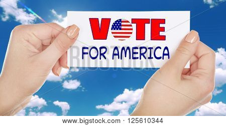 Hands holding Vote for America card on sky background