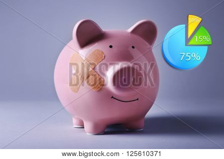 Business accounting concept. Piggy Bank with adhesive bandage on grey background