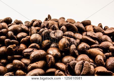 Closeup of coffee beans shot against white background