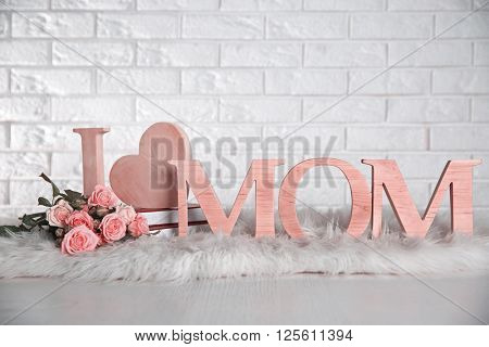 I love mom inscription made of wooden letters with heart on light brick wall background