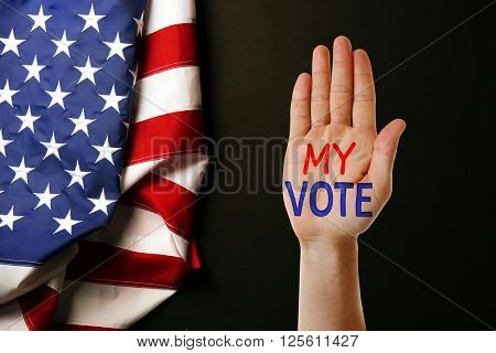 Male hand with text My Vote and USA National Flag on black background
