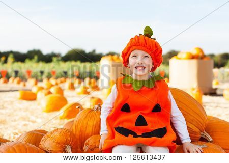 little smiling boy in pumpkin costume sitting at the huge pile of pumpkins and enjoying fall and pumpkin patch time