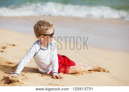 little boy in glasses and rashguard lying at the beach at kauai island hawaii