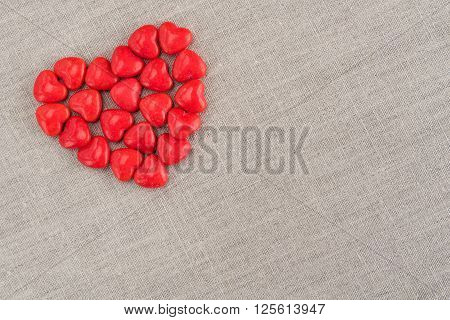 Red heart candy in a heart shape on a tan linen background