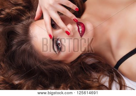 Young sexy woman in bra lying on the bed. She covers her eyes with her hand. Bliss. Girl flirts. Close-up portrait.