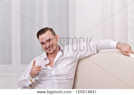 Young romantic man in white shirt. Men's fashion. Shirt with cufflinks. Man sitting on the couch and jokes.