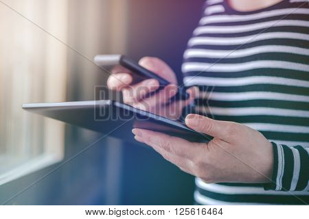 Smartphone and tablet data synchronization woman syncing files and documents on personal wireless electronic devices at home selective focus with shallow depth of field.