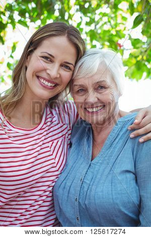Portrait of happy mother and daughter with arm around while standing outdoors