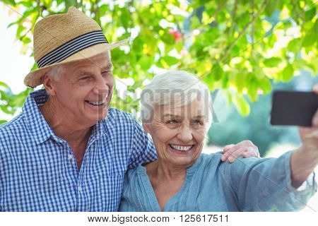 Happy retired couple taking selfie while standing outdoors