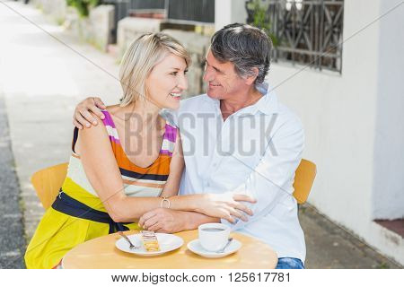 Happy couple sitting with arm around at cafe