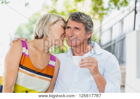 Woman whispering to man at cafe