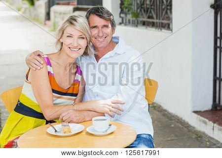 Portrait of couple sitting with arm around at cafe