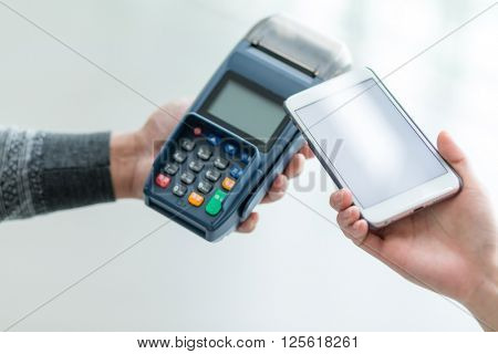 Woman using cellphone to pay with mobile phone