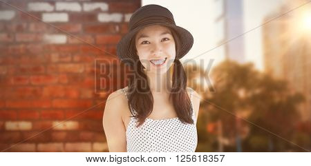 Cheerful woman with a polka dot dress and hat against wall of a house