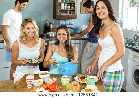 Portrait of happy young women with male friends cooking together in kitchen at home