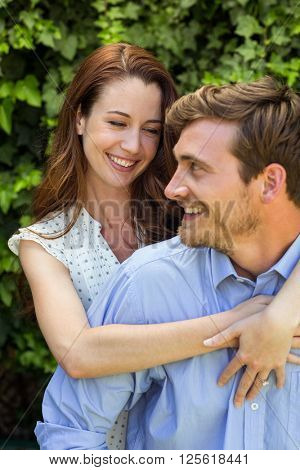 Young smiling couple hugging at front yard