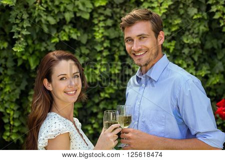 Portrait of happy couple toasting wineglasses at front yard