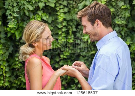 Romantic man wearing ring to woman at front yard
