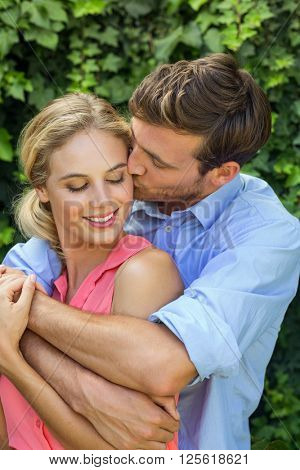 Romantic man hugging while kissing woman at front yard