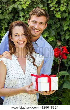 Portrait of happy man giving gift to woman at front yard