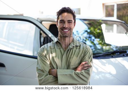 Portrait of smiling pesticide worker with arms crossed while standing by van