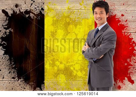 Portrait of a smiling businessman with the arms crossed against belgium flag in grunge effect