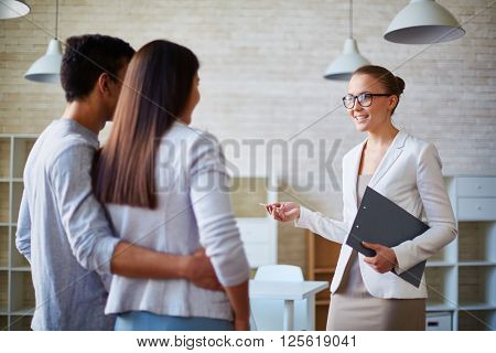 Woman realtor talking to a young family