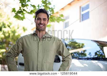Portrait of smiling pesticide workerwith hand on hip while standing by van