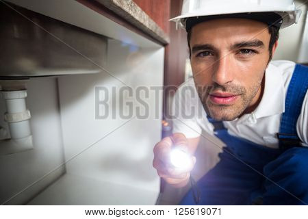 Portrait of man holding illuminated torch while kneeling in kitchen