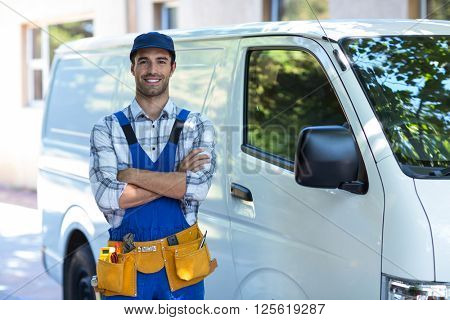 Portrait of happy carpenter with arms crossed while standing by van