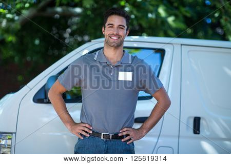 Portrait of happy delivery person with hand on hip while standing by van