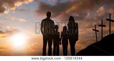 Cheerful family holding hands against cross religion symbol shape over sunset sky