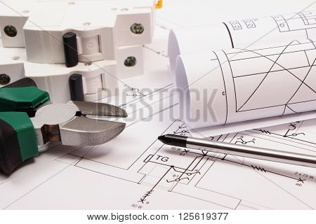 Metal pliers screwdriver electric fuse and rolls of diagrams on electrical construction drawing of house work tool and drawing for projects engineer jobs concept of building house