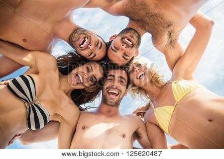 Group of friends standing in circle and smiling at camera on the beach
