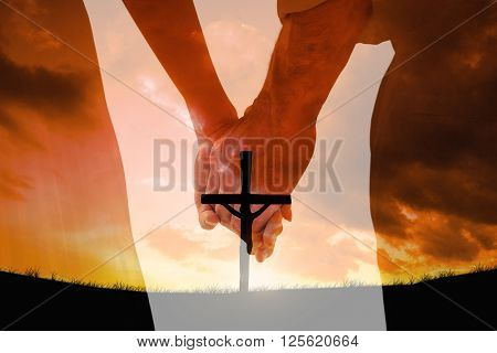 Bride and groom holding hands close up against cross religion symbol shape over sunset sky