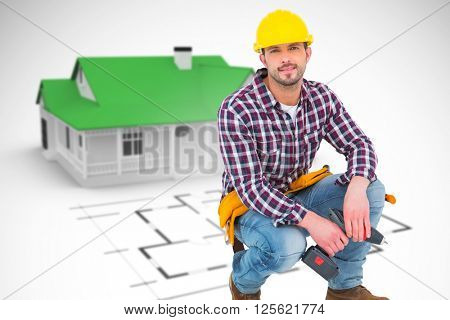 Crouching handyman holding power drill against blue house behind an architectural plan