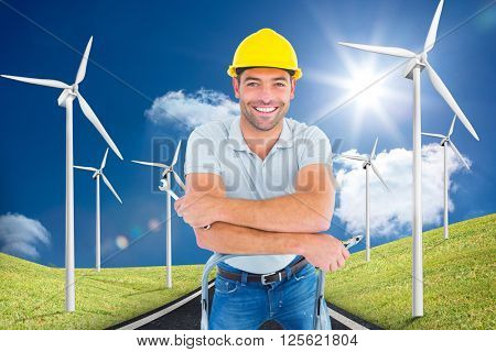 Handyman with hand tools on step ladder against road leading out to the horizon with wind turbines either side
