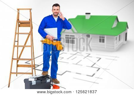 Carpenter on the phone against blue house behind an architectural plan