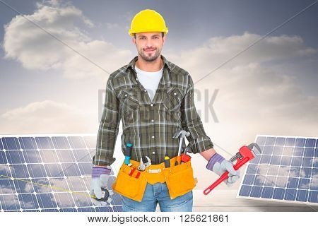 Manual worker holding various tools against solar panels on floorboards in the sky