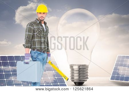 Manual worker with spirit level and toolbox against light bulb and solar panels on floorboards in the sky